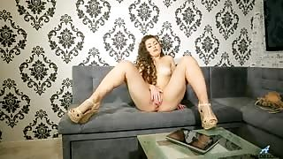 Gorgeous amateur milf with long locks of curls and a juicy round ass strips down to nothing but her high heels and massages her cum hungry snatch and sensitive clit